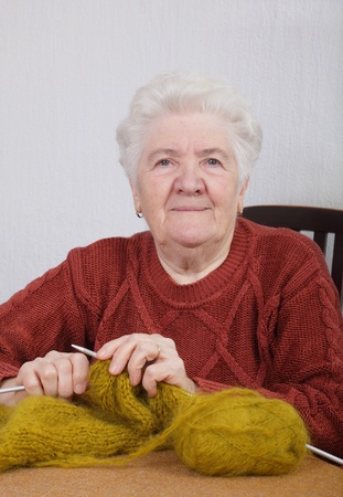Portrait of a senior woman knitting in her room photo