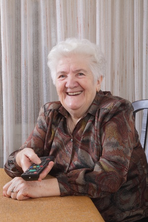 Portrait of a senior woman watching TV in her room Stock Photo - 8629268