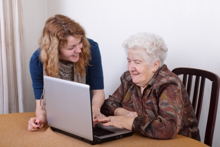 Young girl teaching senior woman to work at computer