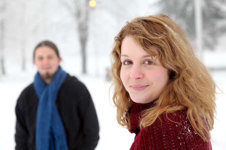 Beautiful smiling teenage girl in a cold winter day with a man in background photo