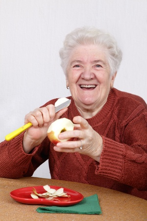 Portrait of a smiling senior woman eating apple photo