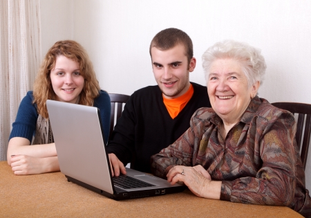 Young girl and boy teaching senior woman to work at computer Stock Photo - 8808163