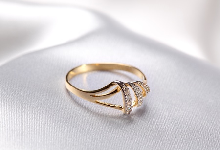 Close up shot of a golden  ring at white textile background Stock Photo