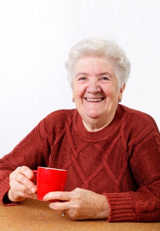 Smiling senior  woman with a cup of coffee in hands