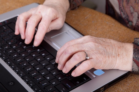 Hands of an old  woman on a computer keyboard Stock Photo - 9116488