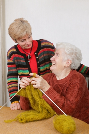 Senior and mature womans speaking  laughing  and learning knitting photo