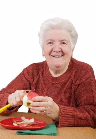 Portrait of a smiling senior woman eating apple isolated on white photo