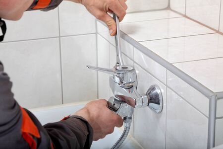 Plumber hands fixing water  tap with spanner Stock Photo