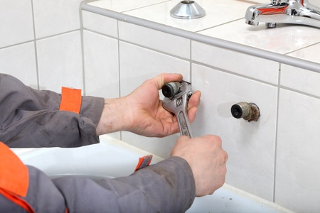 Plumber hands fixing water pipe with spanner Stock Photo - 9283622