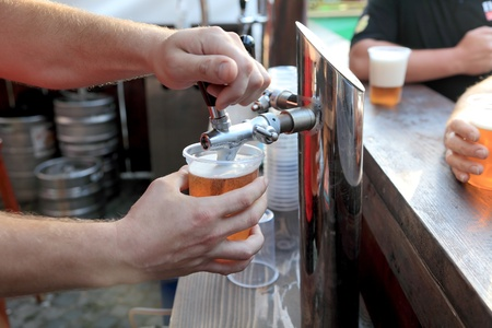 Pouring  beer to plastic glass from beer tap photo