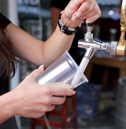 pouring beer: Pouring  beer to plastic glass from beer tap