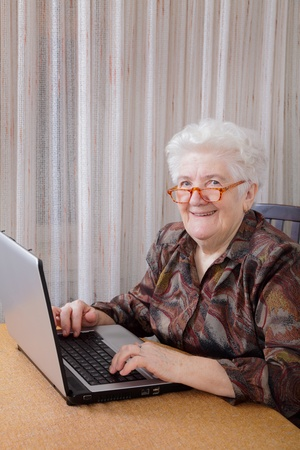 Portrait of smiling senior woman working at computer photo