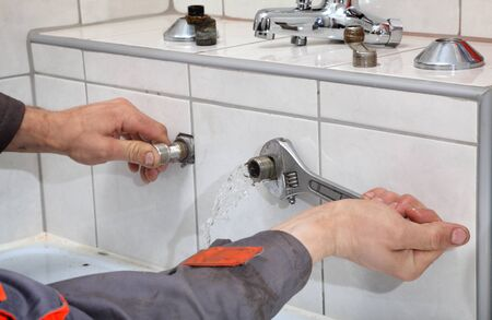 bathroom equipment: Plumber hands fixing water pipe with spanner and with leaking water from pipe Stock Photo