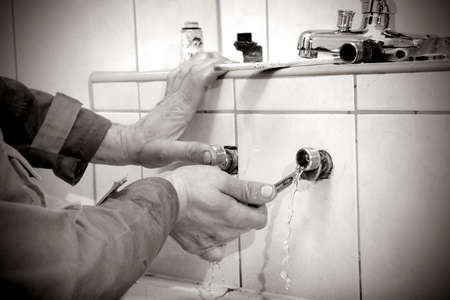 Plumber hands fixing water pipe with spanner and with leaking water from pipe photo