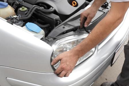 Repairing of modern car, workers hands fixing car light photo