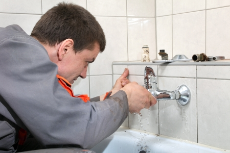 pipe wrench: Plumber fixing water pipe in a bathroom