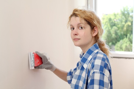 plasterboard: Young girl  sanding wall in her home