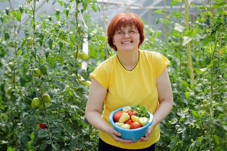 Red hair woman holding vessel with fresh vegetable in garden photo