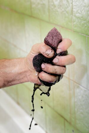 Human hand squeezing dirty sponge after cleaning