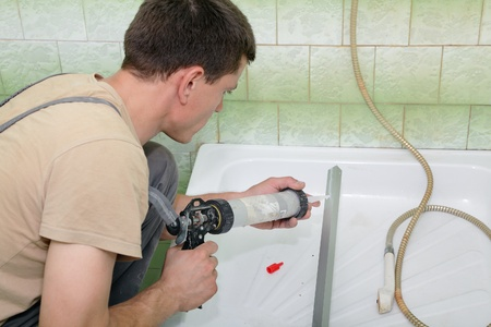 Plumber using silicone cartridge for fixing aluminum batten of shower cabin