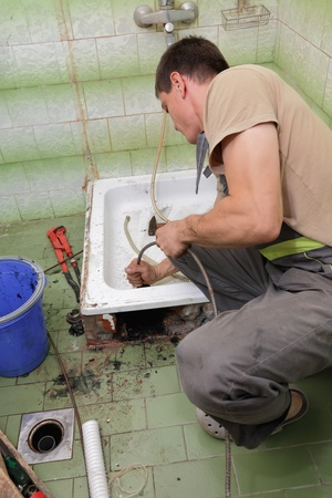 sink drain: Plumber cleaning  drain in bathroom with cable