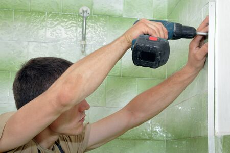 Plumber using electric screwdriver  for fixing aluminum batten of shower cabin Stock Photo