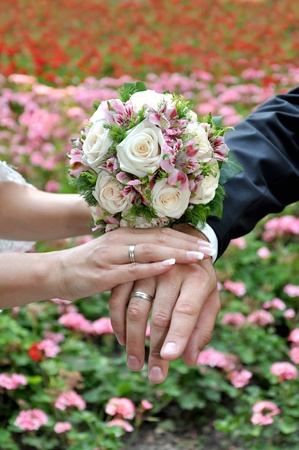Bride and groom hands with bouquet of roses photo
