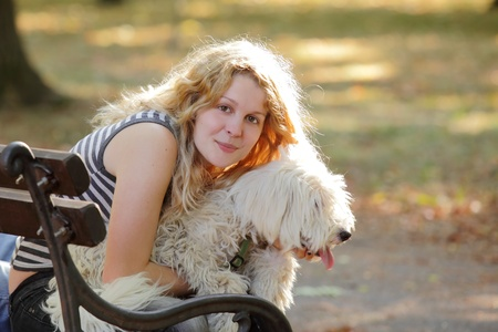 Young girl sitting at bench and hugging white dog photo
