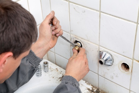 Plumber fixing pipeline  with tool in hands