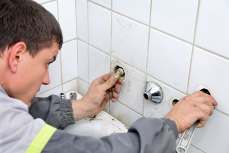 Plumber fixing pipeline  with tool in handsand checking leaking Stock Photo