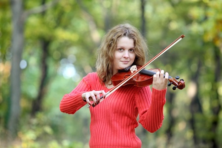 Young smiling Caucasian girl in  forest with violin photo