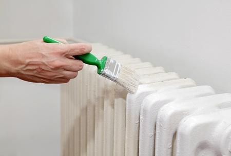 Painting of retro white radiator with brush