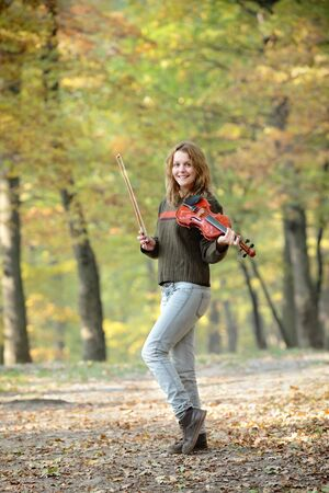 Young smiling Caucasian girl in  forest with violin Stock Photo - 11365178