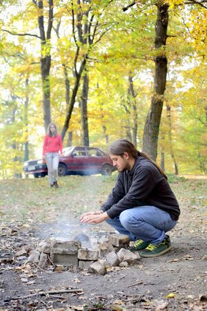 Young man at picnic warming hands at campfire photo