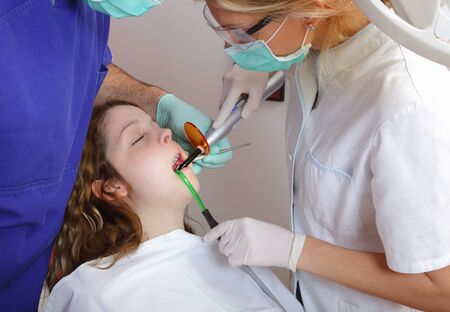 curing: Female dentist and assistant using dental UV curing light Stock Photo