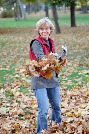 groundskeeper: Smiling mature woman raking leaves in a garden