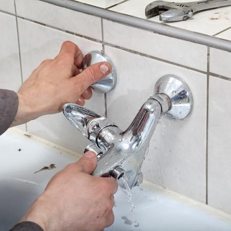 llave de agua: Manos fontanero fijar el agua del grifo con fugas de agua Foto de archivo