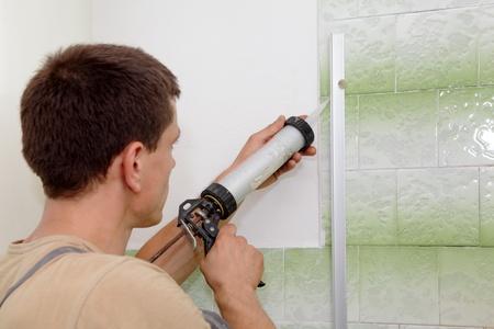 cabine de douche: Plombier utilisant la cartouche de silicone pour la fixation en aluminium latte de la cabine de douche Banque d'images
