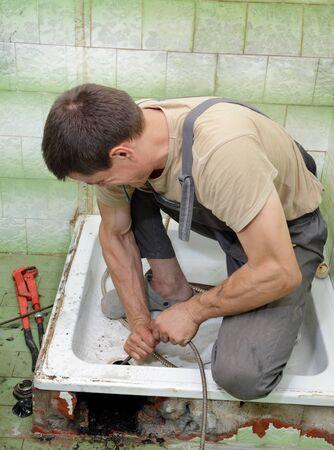 desague: Fontanero fuga de limpieza en el baño con un cable