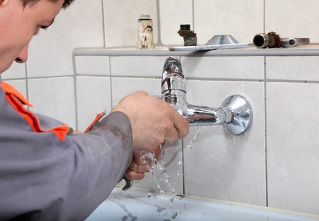 Plumber  fixing water  tap with leaking water photo