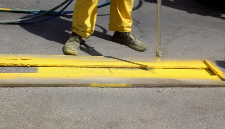 Hand spraying of yellow line for bus station