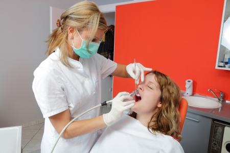polishing: Female doctor cleaning and polishing  young patient tooth