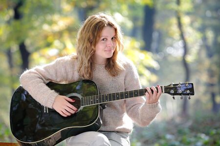 Young Caucasian girl in  forest with guitar, selective focus photo