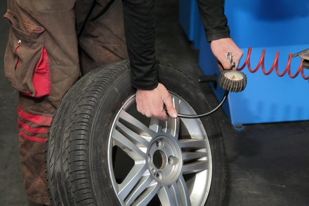 Checking the air pressure in a tire with a pressure gauge photo