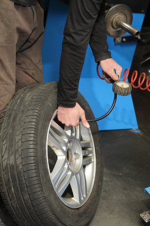 Checking the air pressure in a tire with a pressure gauge Stock Photo - 13109373