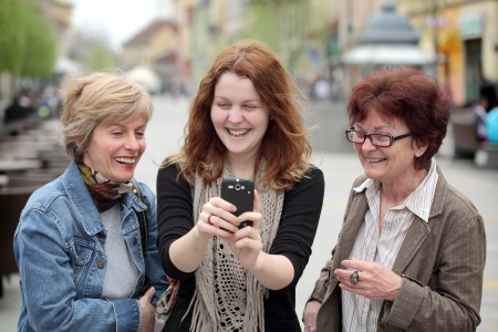 Mother, daughter and aunt looking to mobile phone and laughing photo
