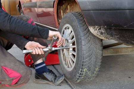 Mechanic working on a car tire in service using cross wrench