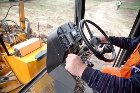 Driving a grader at construction site, real people