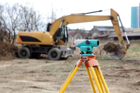Theodolite on tripod with buldozer in background photo