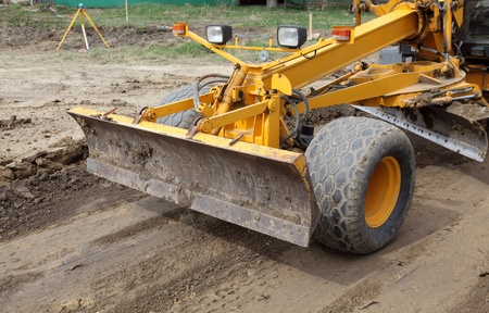 leveler: Close up of grader blade at road construction site